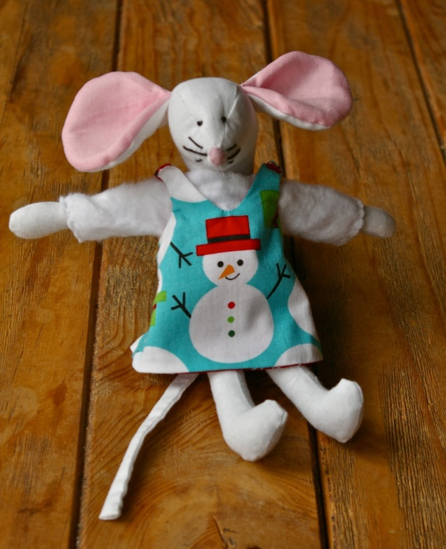 Ellen Mouse shows snowman side of her reversible pinafore