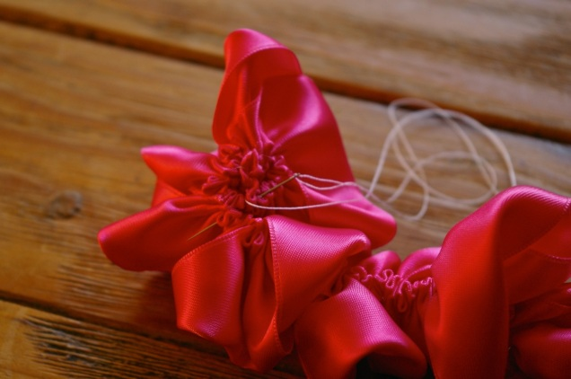 roll up the gathered ribbon, keeping the gathered edge level, and stitch it in place as you go